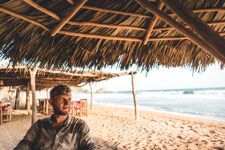 Thoughtful Young Man Sitting On Beach