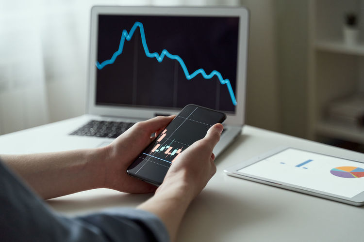 Millennial male shareholder using phone business app and buying stocks on laptop