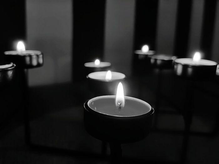 Close-up of lit tea light candles in darkroom