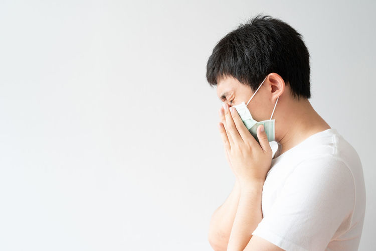 Side view of mature man using smart phone against white background
