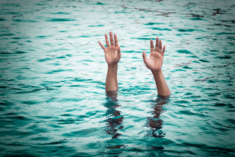 Cropped image of person with arms raised in sea