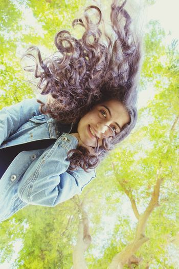 Directly Below Portrait Of Smiling Young Woman Against Trees