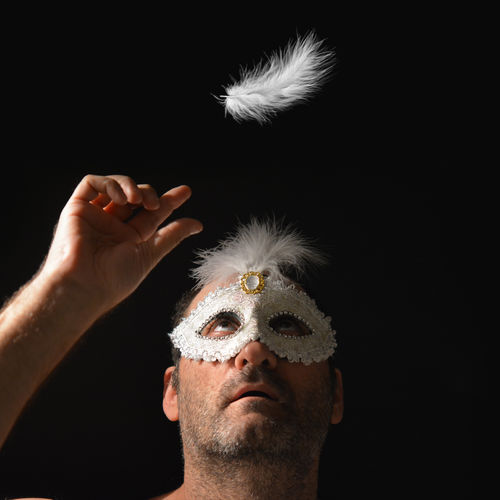 Man Wearing Carnival Mask Reaching For Feather Against Black Background
