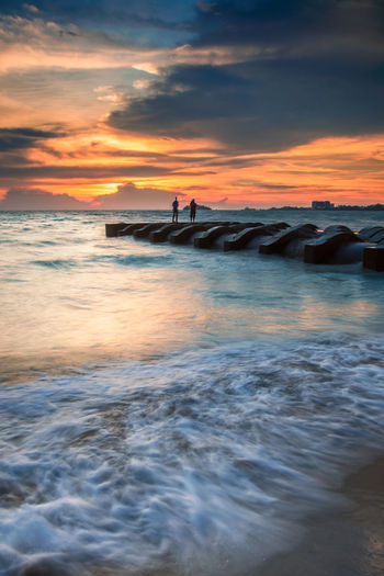 Silhouette of people standing on drainage pip in the sea at sunset