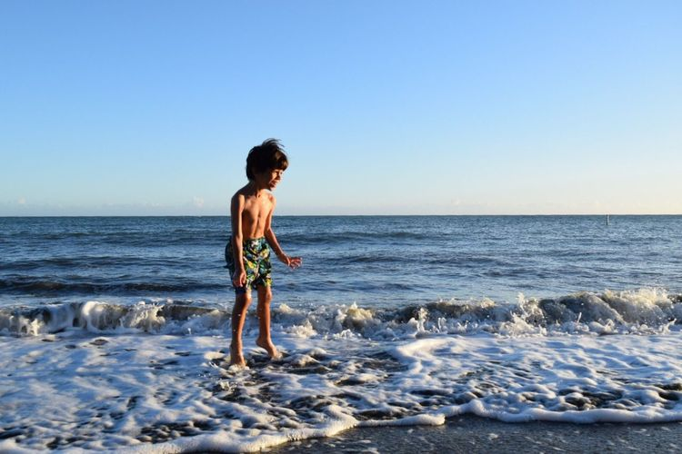 Boy Playing On Shore Against Clear Sky