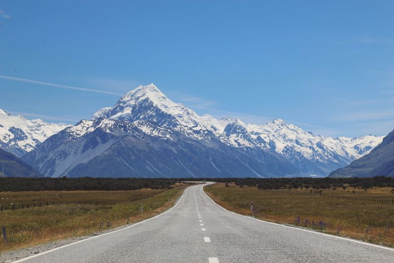 Scenic view of road against snowcapped mountains
