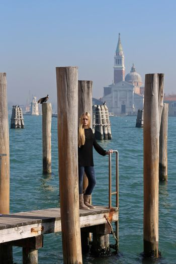 Young woman standing on pier over grand canal against sky with san marco campanile in background