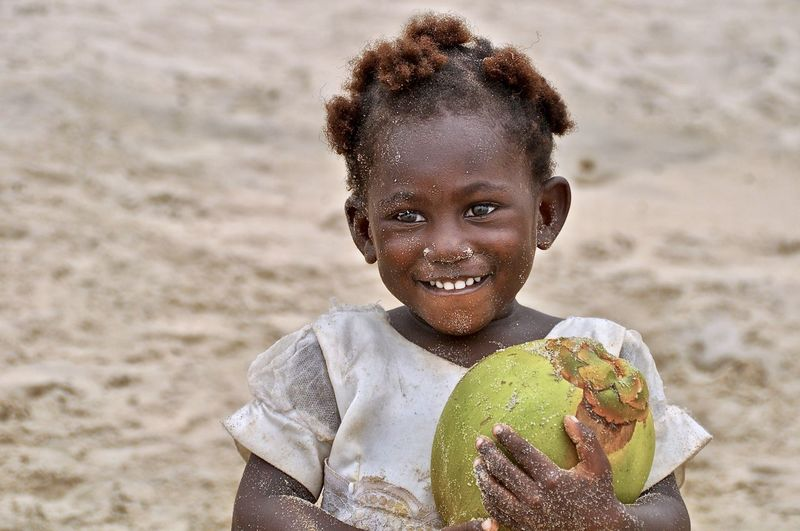 Portrait of messy smiling girl holding coconut at beach
