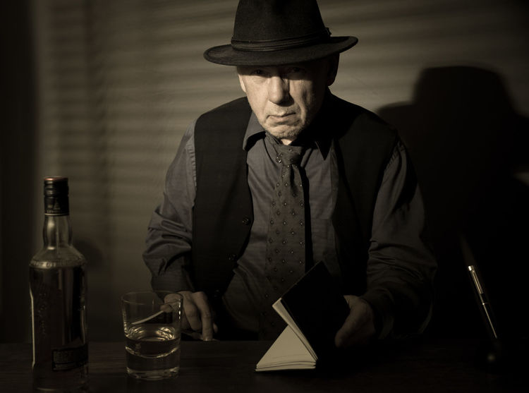 Film Noir reloaded: The dirty old detective in his bureau talking to a new client Acting Adult Desk Hat Alcohol Bottle Detective Fountainpen Monochrome Notebook Old Person Old Person Sitting One Man Only One Person Studio Shot Table