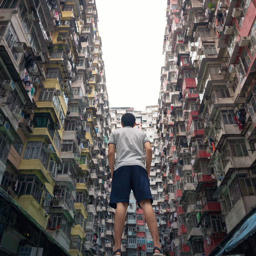 Rear view of man standing amidst buildings in city