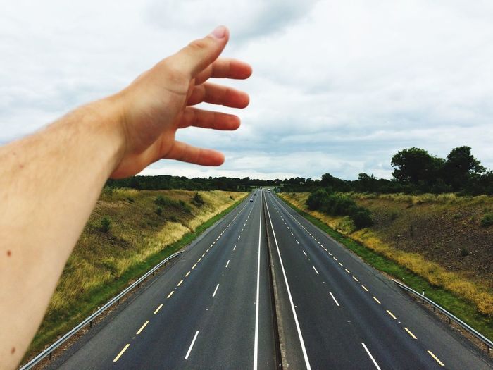 Cropped hand above two lane highway