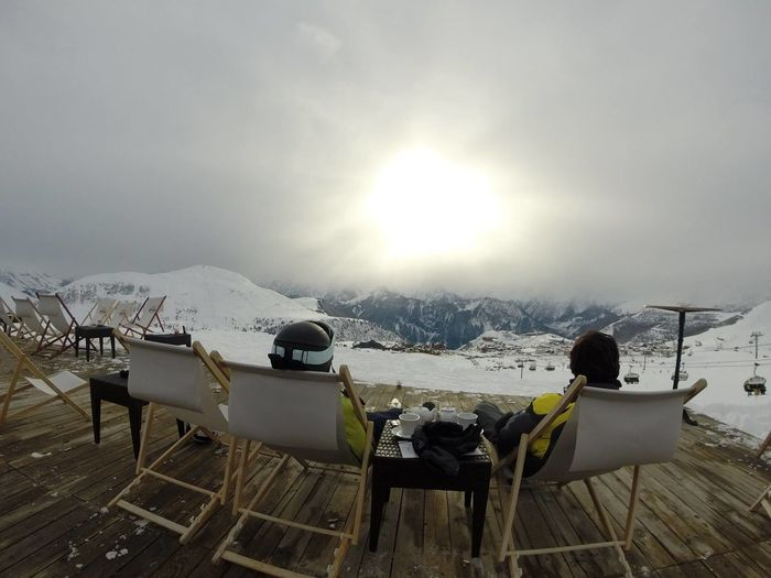 Rear View Of Male Friends Relaxing On Deck Chairs At Alpe D Huez