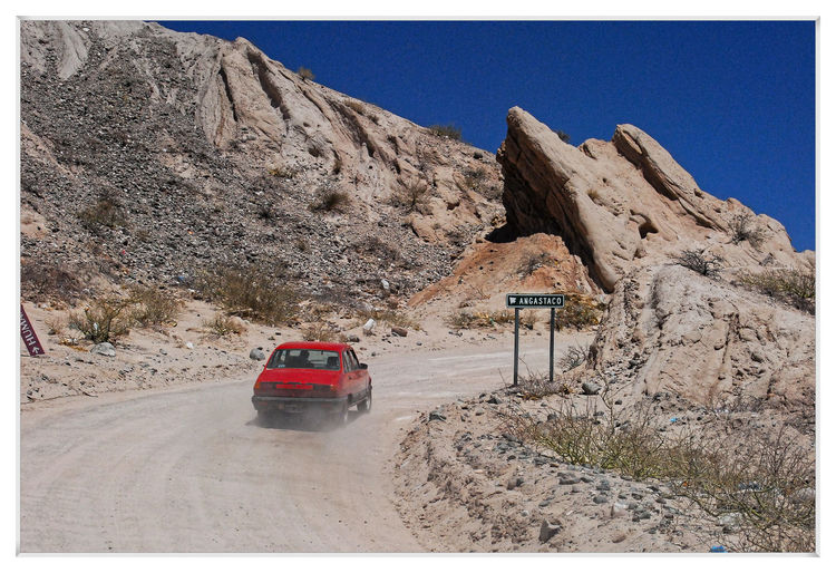 Cars on road by rock formation against clear sky
