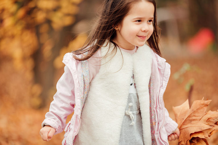 Cute smiling girl holding autumn leaf standing outdoors