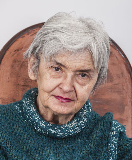 Close-up portrait of senior woman sitting on chair