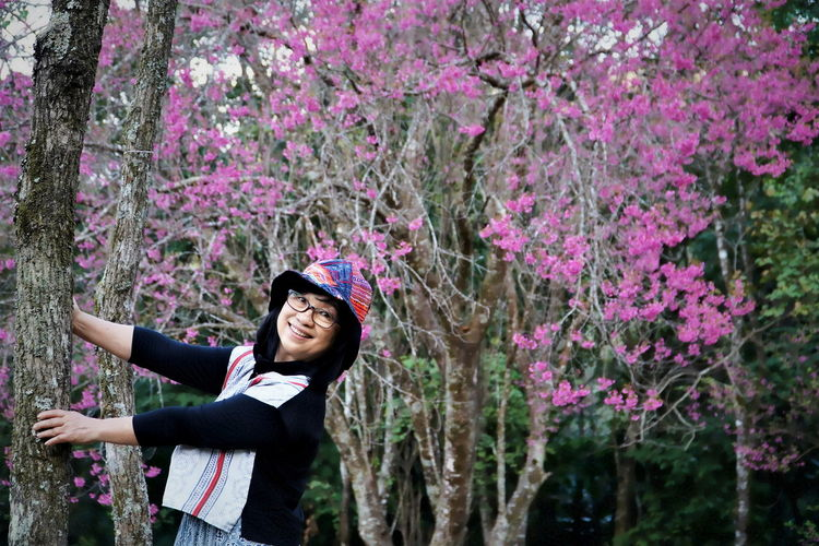 Smiling woman standing by pink flowering tree