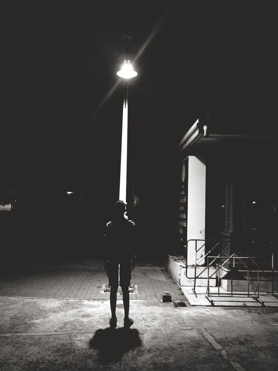 Full Length Rear View Of Man Standing On Illuminated Footpath At Night
