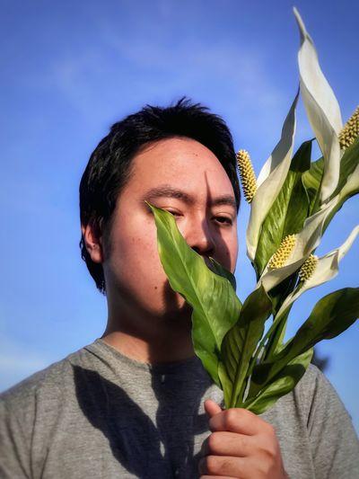 Portrait of man holding flower against sky