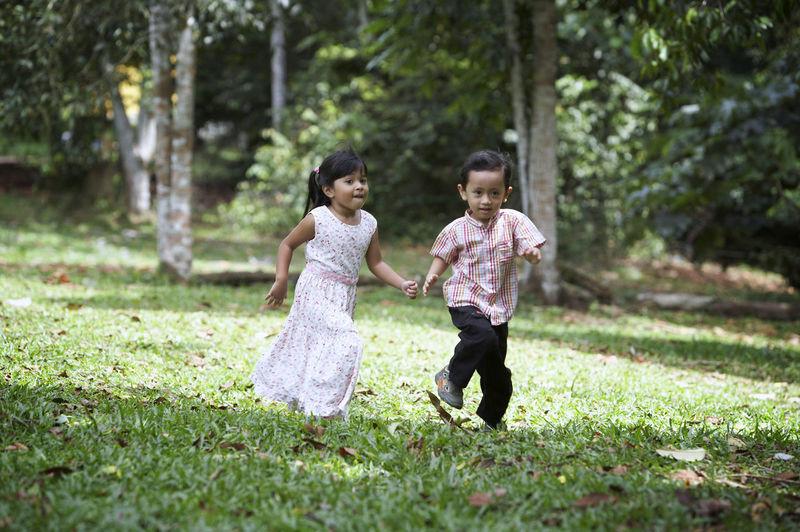 Siblings Running On Grassy Field At Park