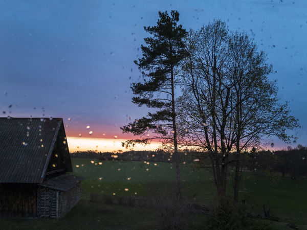 Raindrops on glass. Night view through window. Old barn, trees, sunset. Architecture Barn Beauty In Nature Building Exterior Built Structure Clear Sky Countryside Day Field Grass Growth Landscape Nature No People Rain Raindrops Rural Sky Sunset Through Through The Window Tree Twilight Weather Wet