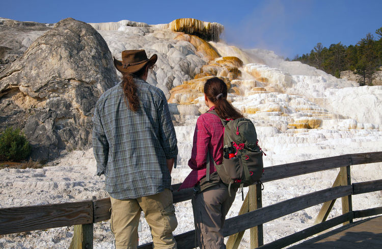 Tourists in the Mammoth Hot Springs Historic District ,Yellowstone National Park Leisure Activity Two People Real People Nature Mountain Togetherness Standing People Beauty In Nature Outdoors Yellowstone National Park Mammoth Hot Springs Area Geothermal Activity Hot Spring Hot Springs Terraces Geology Travertine Terraces Tourist Tourism Exploring Travel Destinations Crystallized Calcium Carbonate Mammoth Hot Springs Historic District Nature_collection Volcanic Landscape