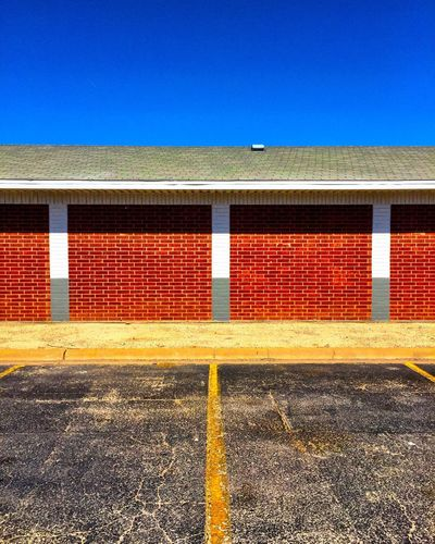 Day No People Outdoors Blue Architecture Built Structure Clear Sky Multi Colored Sky Symmetry Parking Lot Striping Brick Wall