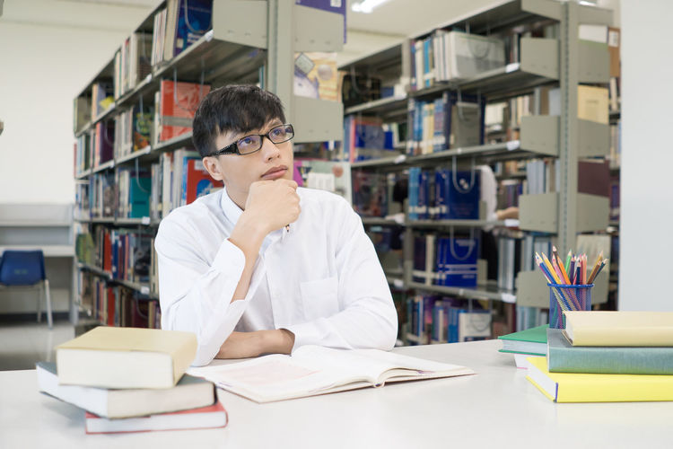 Thoughtful Male Student Studying At Table In Library