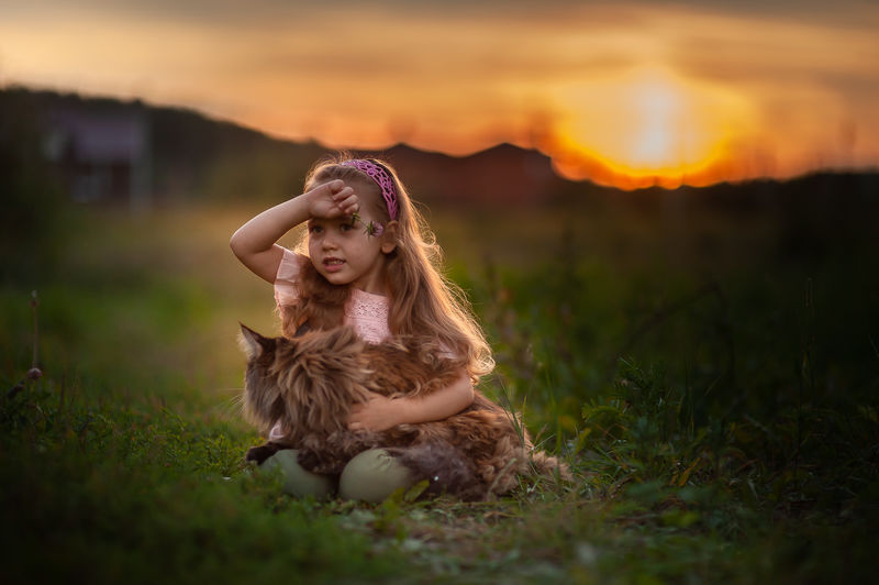 Smiling girl with cat sitting on grass
