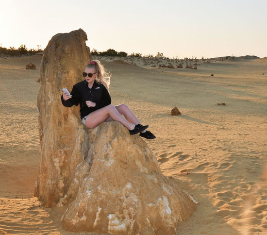 Young woman taking selfie on limestone rock in the Pinnacle Desert in Nambung National Park in Western Australia. Adventure Beach Beauty In Nature Cell Phone  Desert Happiness Landscape Limestone Nambung National Park Nature One Person Outdoors People Pinnacles Rock Sand Sand Dune Selfie Sitting Sunset Sunset_collection Twilight Vacations Western Australia Young Adult
