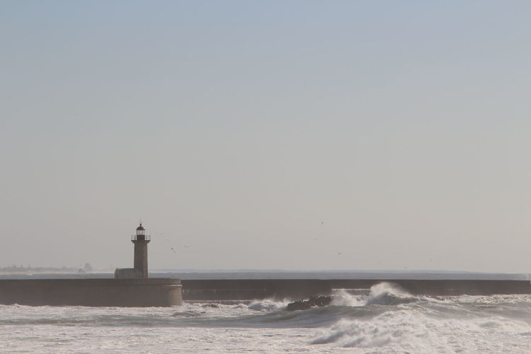 Lighthouse on pier in sea against clear sky