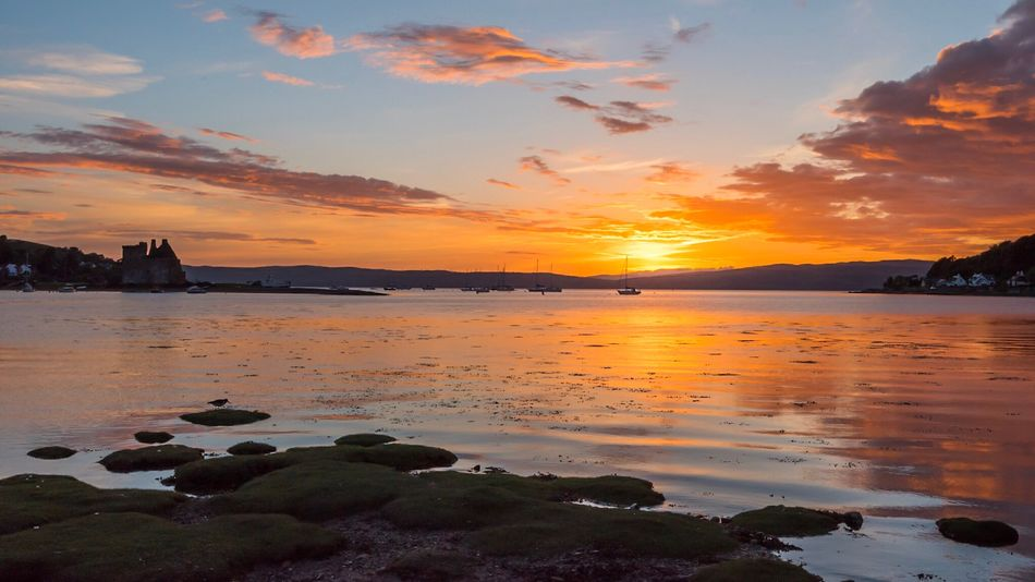 Sunset with Lochranza Castle on the Isle of Arran on the East Coast of Scotland Sunset Water Sky Beauty In Nature Nature Sea Scenics Tranquil Scene Tranquility Cloud - Sky No People Lochranza Scotland Scotland Isleofarran
