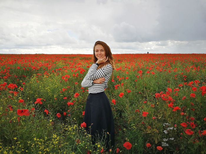 Portrait Of Woman Standing At Red Poppy Farm Against Cloudy Sky