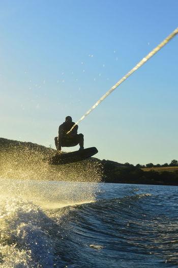 Man waterskiing on sea against sky