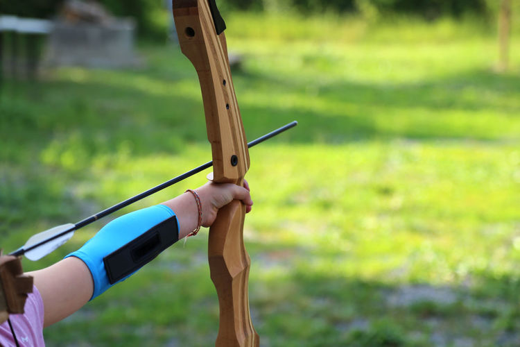 Cropped hands of person practicing archery