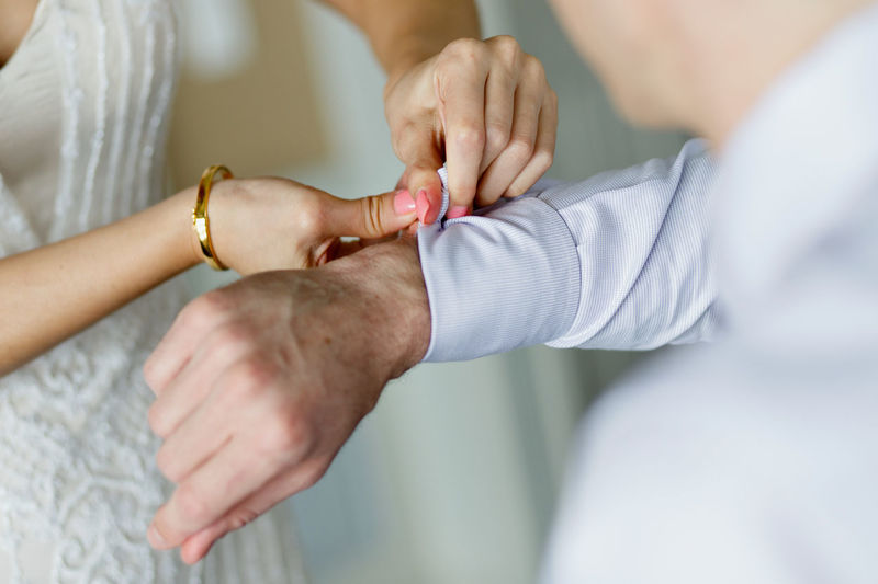 The bride helps her fiance to fasten cufflinks Human Hand Hand Human Body Part Two People Adult Men Midsection Women Selective Focus Indoors  Close-up Occupation People Togetherness Body Part Finger Cufflinks Button Helping Bride And Groom Getting Ready Fashion Man Fashion
