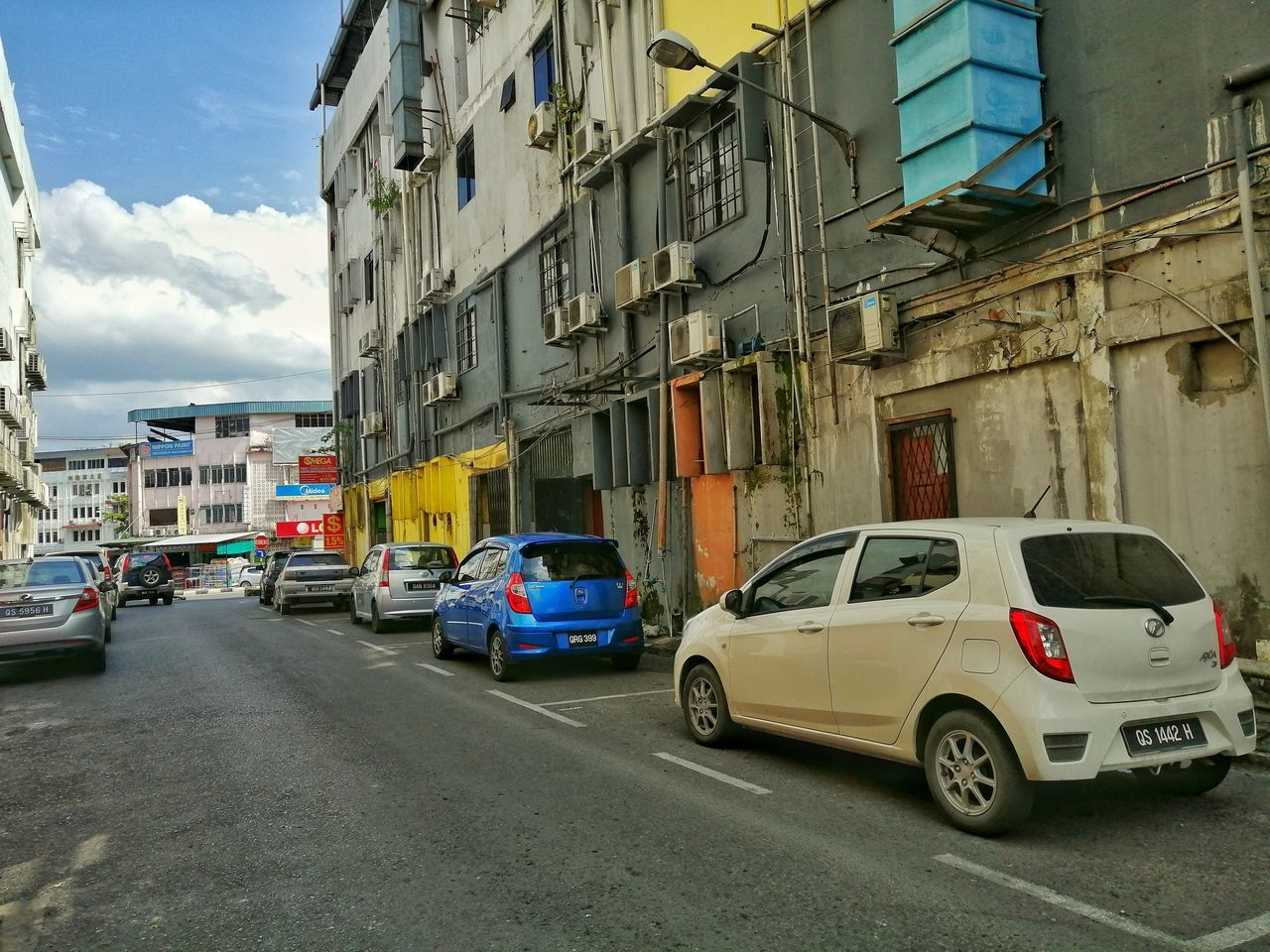 TRAFFIC ON ROAD BY BUILDINGS IN CITY