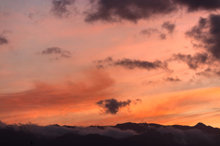 Low angle view of silhouette mountains against romantic sky