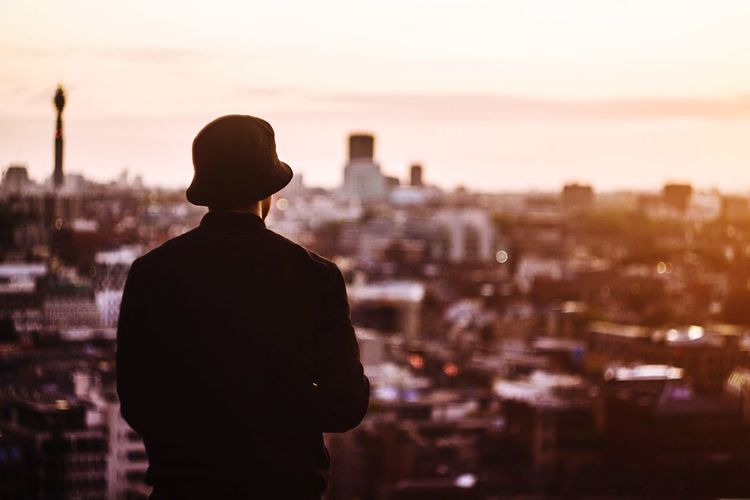 Rear view of man standing in city at sunset