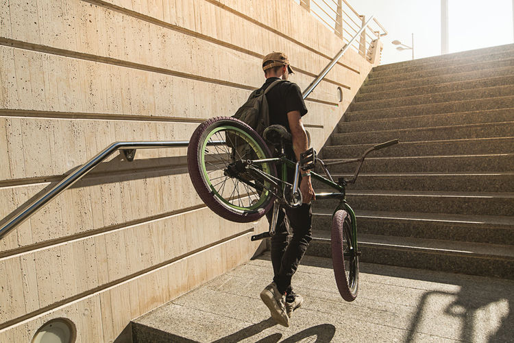 Man with bicycle on staircase