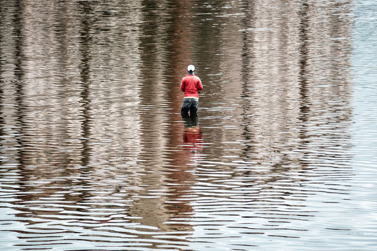 Rear view of person angling in lake