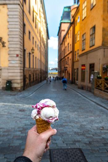 Hand holding ice cream cone on street