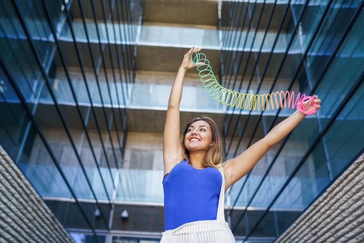 Low angle view of young woman exercising with coiled spring against building