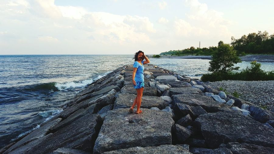 Full length of young woman standing on rock by sea