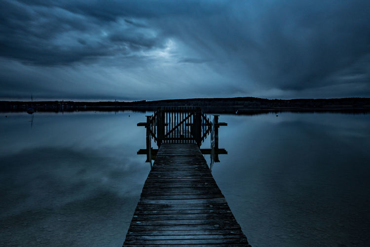 Pier Over Lake Against Sky At Dusk