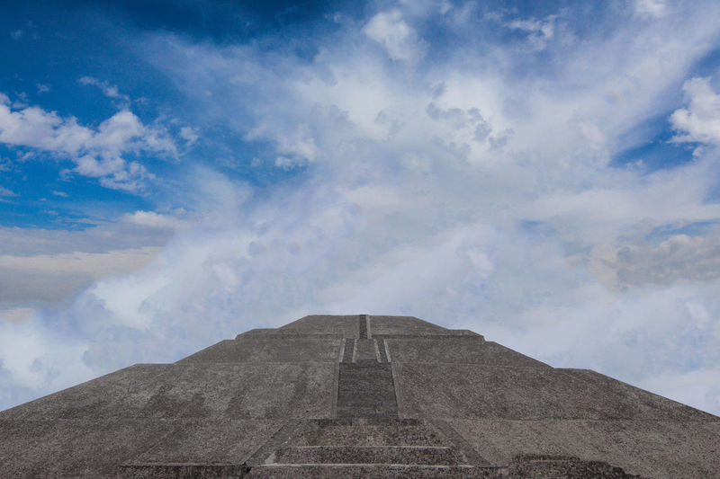Low angle view of pyramid against cloudy sky