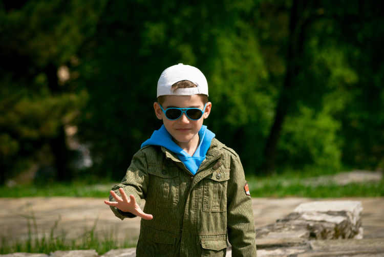 Portrait of boy with sunglasses and cap gesturing while against trees