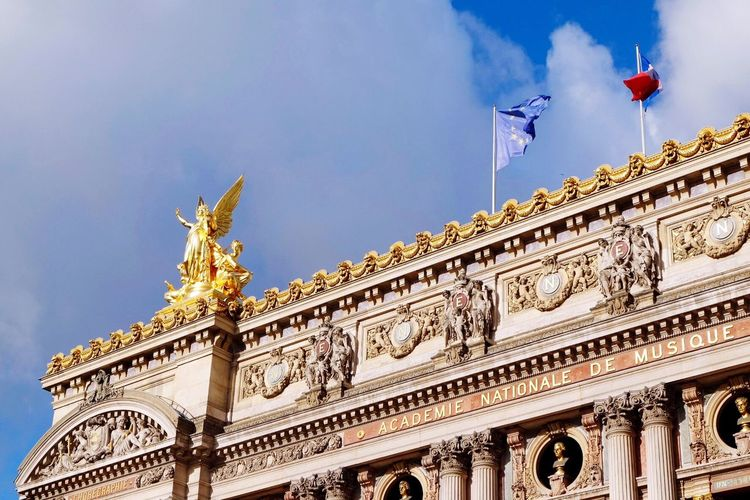 Low angle view of gold statue with flags at palais garnier against sky