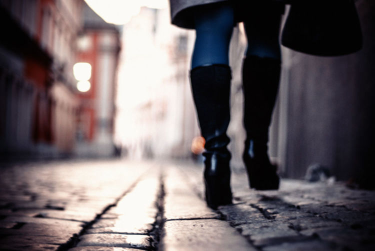 Low section of woman walking on footpath