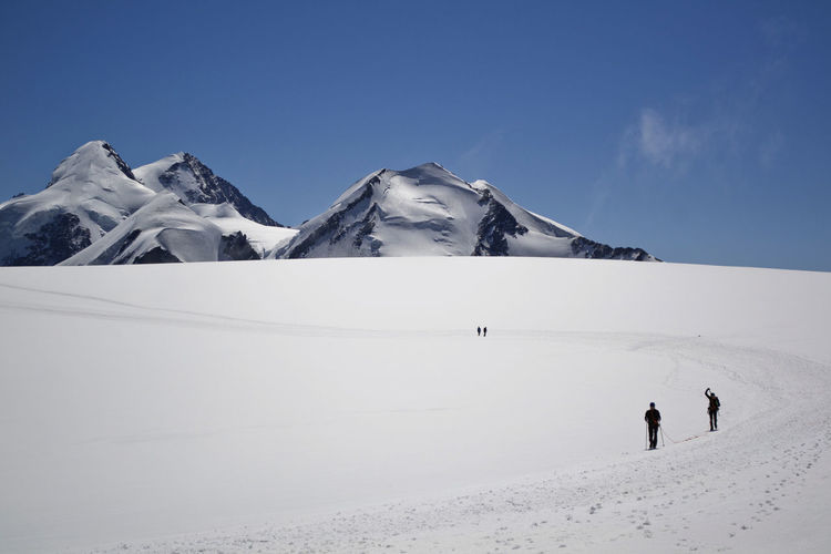 People on snowy land by mountains against sky during winter