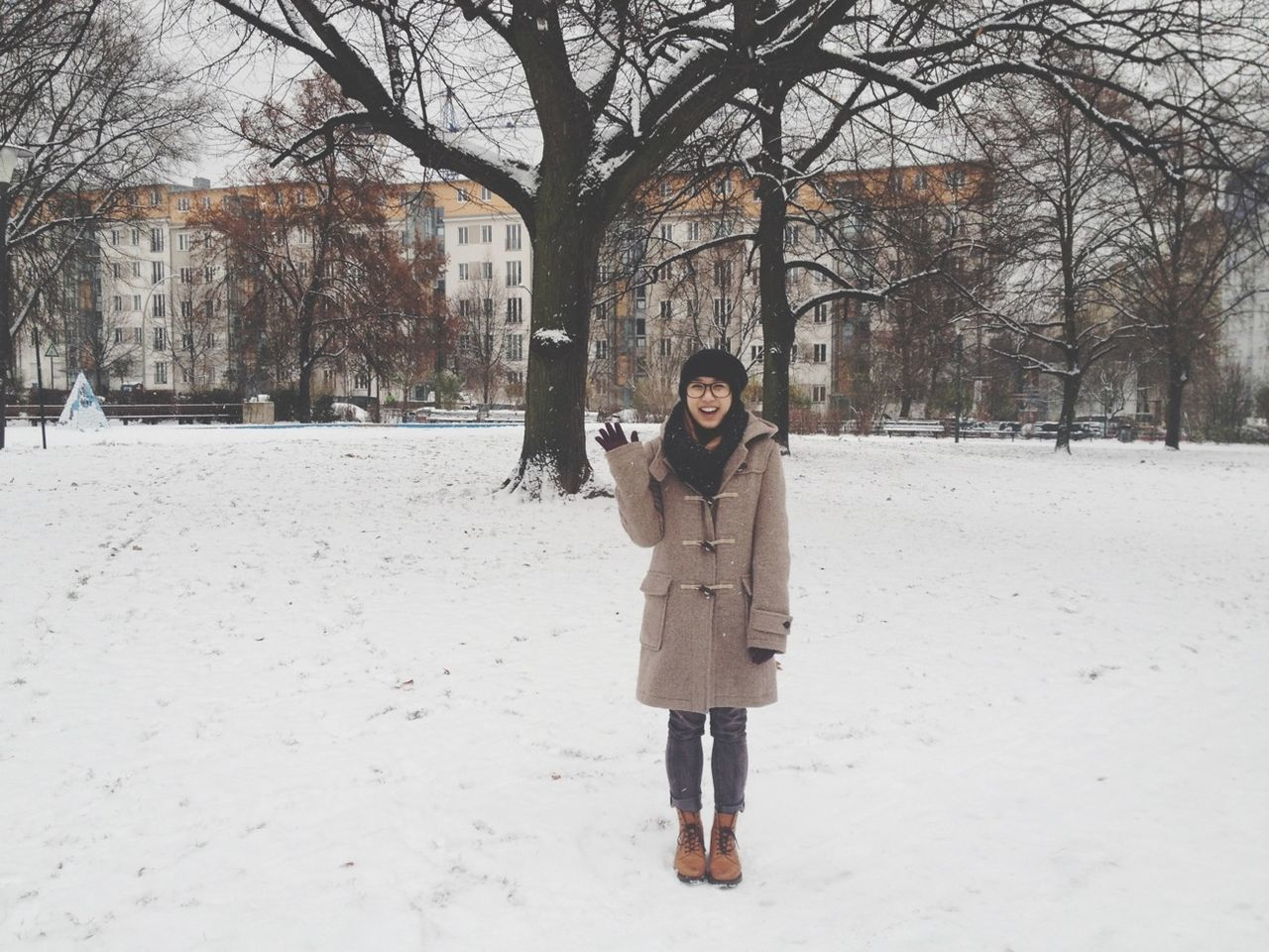 Happy woman standing on snow covered park against bare trees and buildings